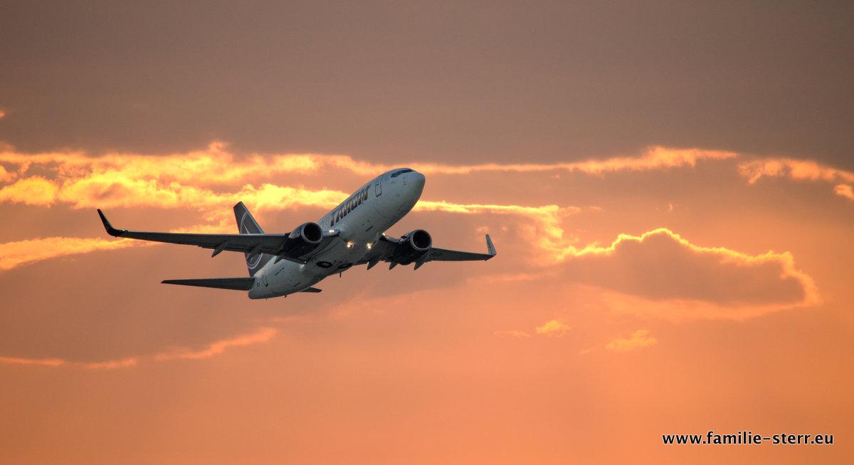 Flugzeug startet in den Abendhimmel / Flughafen München