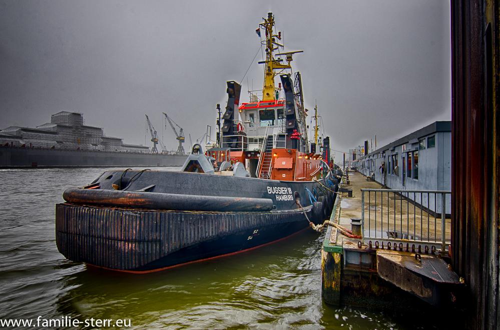 """Schlepper """"Bugsier 18"""" im Hafen Hamburg an den St. Pauli Landungsbrücken im Nebel"""