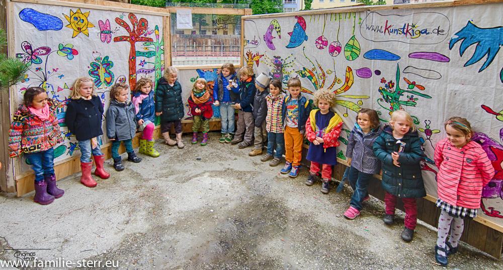 die jungen Künstler vor dem Plakat am Josephsplatz