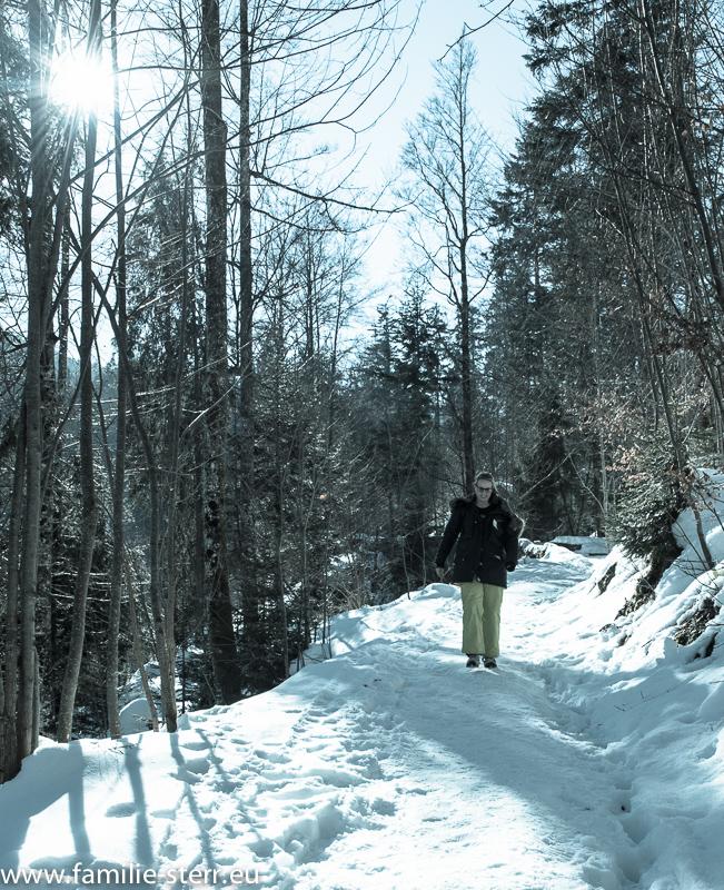 Katharina auf dem verschneiten Weg durch den Wald zum Tatzlwurm