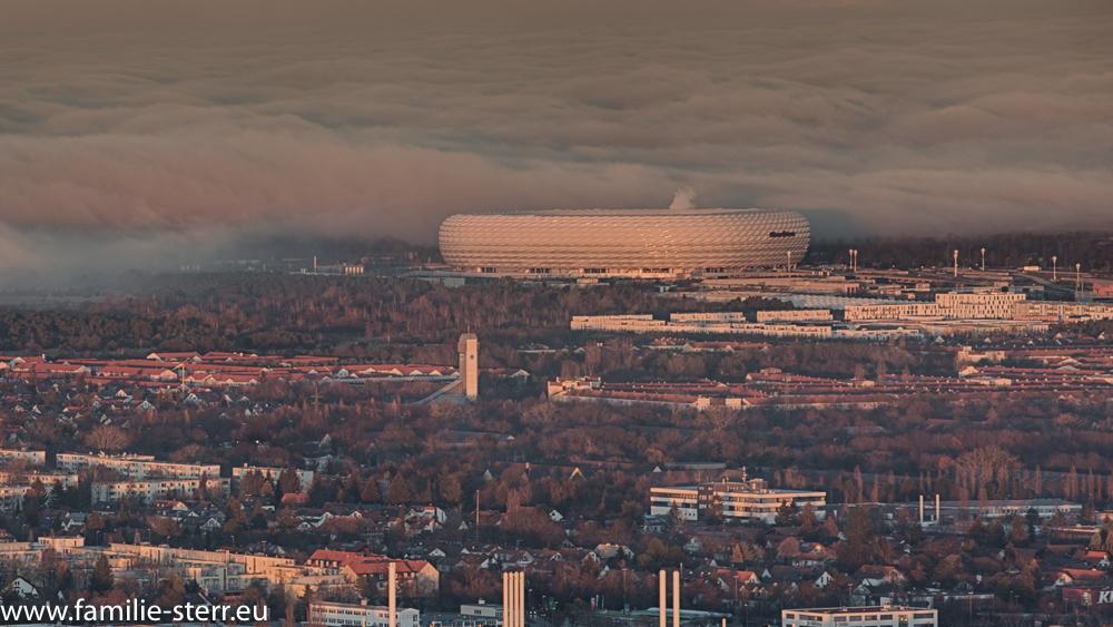 Allianz - Arena vor heranziehender Nebelwand vom Olympiaturm aus gesehen