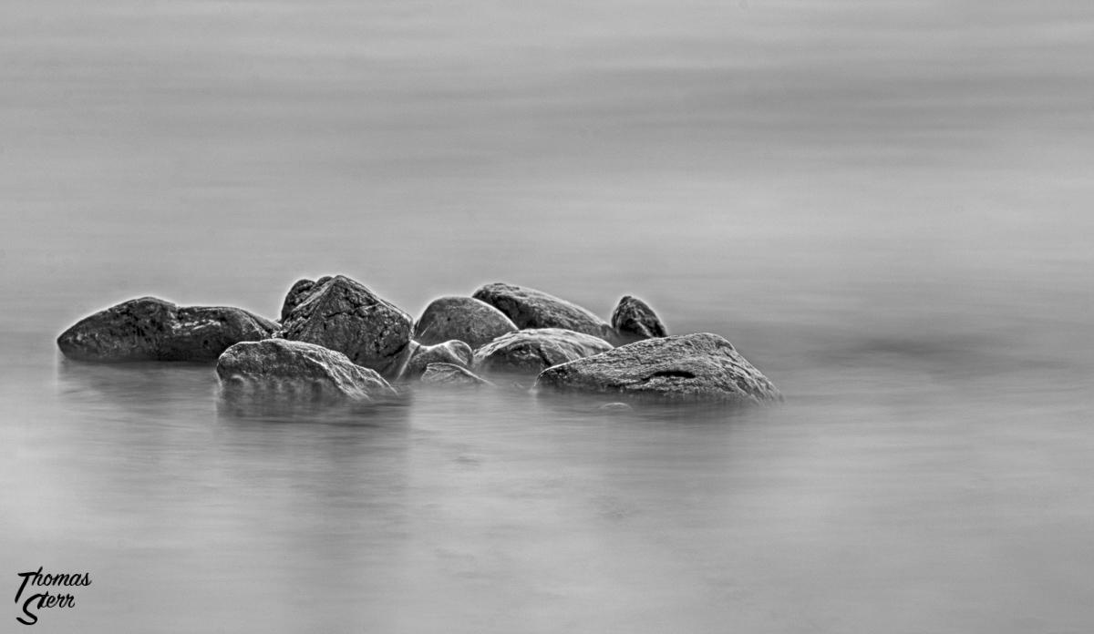 Steine in den Wellen des Sees