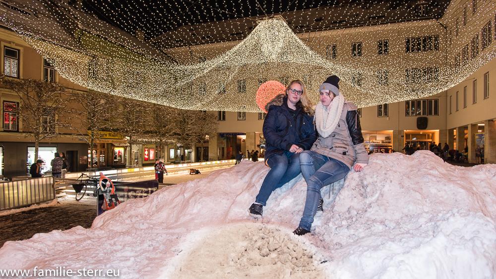 Katharina und Melanie auf einem Schneeberg vor der Eisbahn am Villach Rathaus