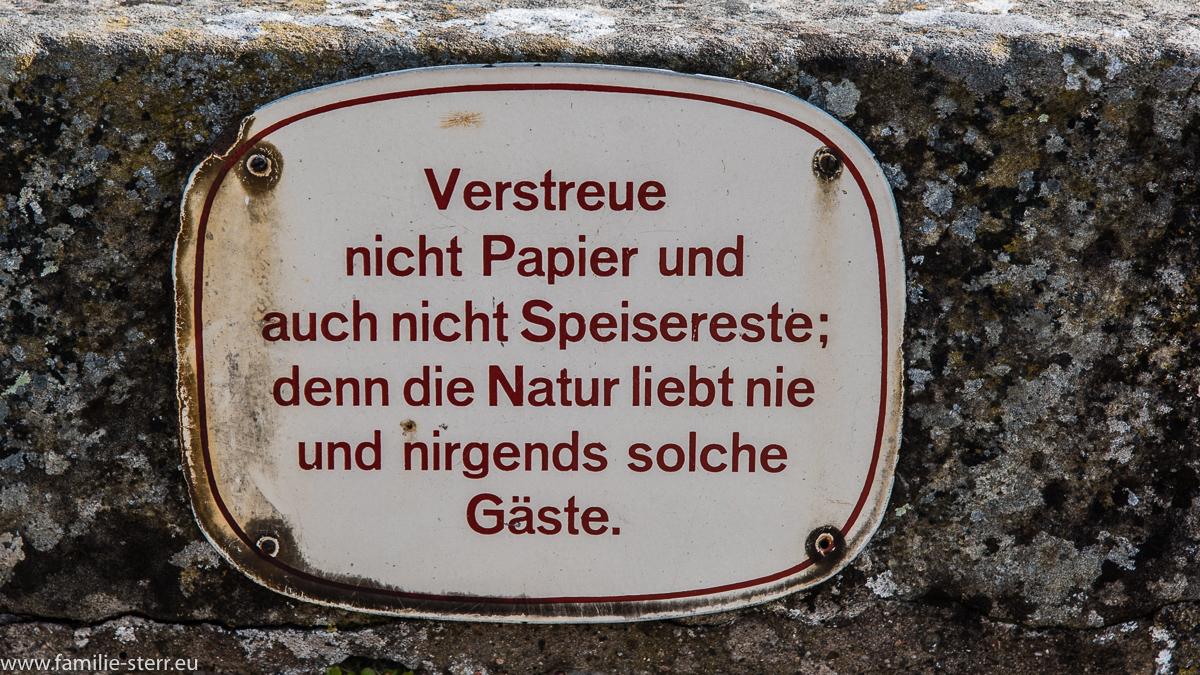 """Schild """"Verstreue nicht Papier und auch nicht Speisereste, denn die Natur liebt nie und nirgends solche Gäste"""""""
