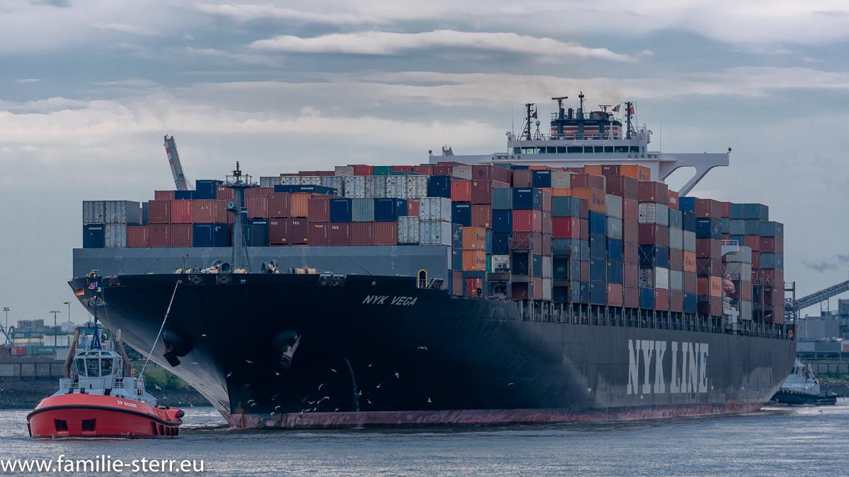 Das Containerschiff NYK Vega wird aus dem Hamburger Hafen in die Elbe geschleppt