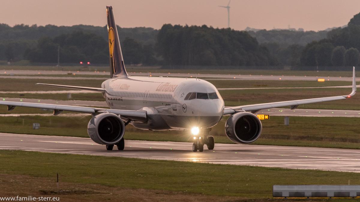 Lufthansa Airbus A320neo D-AINA rollt durch den Sonnenuntergang zum Start auf der nördlichen Startbahn in München