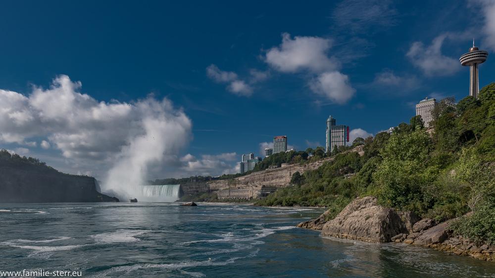 Blick vom Fluss aus zu den kanadischen Fällen und zum Ort Niagara Falls (Ontario)