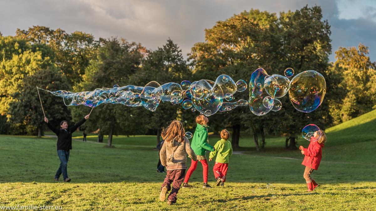 spielende Kinder mit Riesen - Seifenblasen im Englischen Garten in München