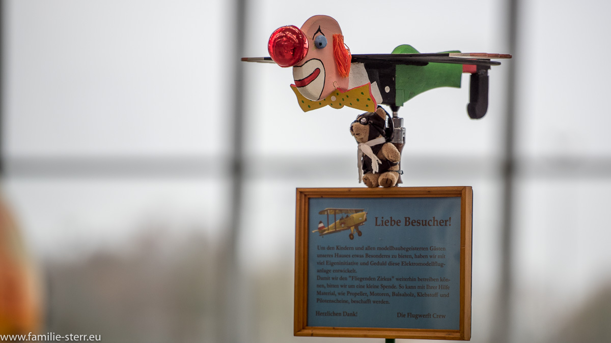 """Clown - Flugzeug und Schild am Eingang zum """"Fliegenden Zirkus"""" in der Flugwerft Oberschleißheim"""