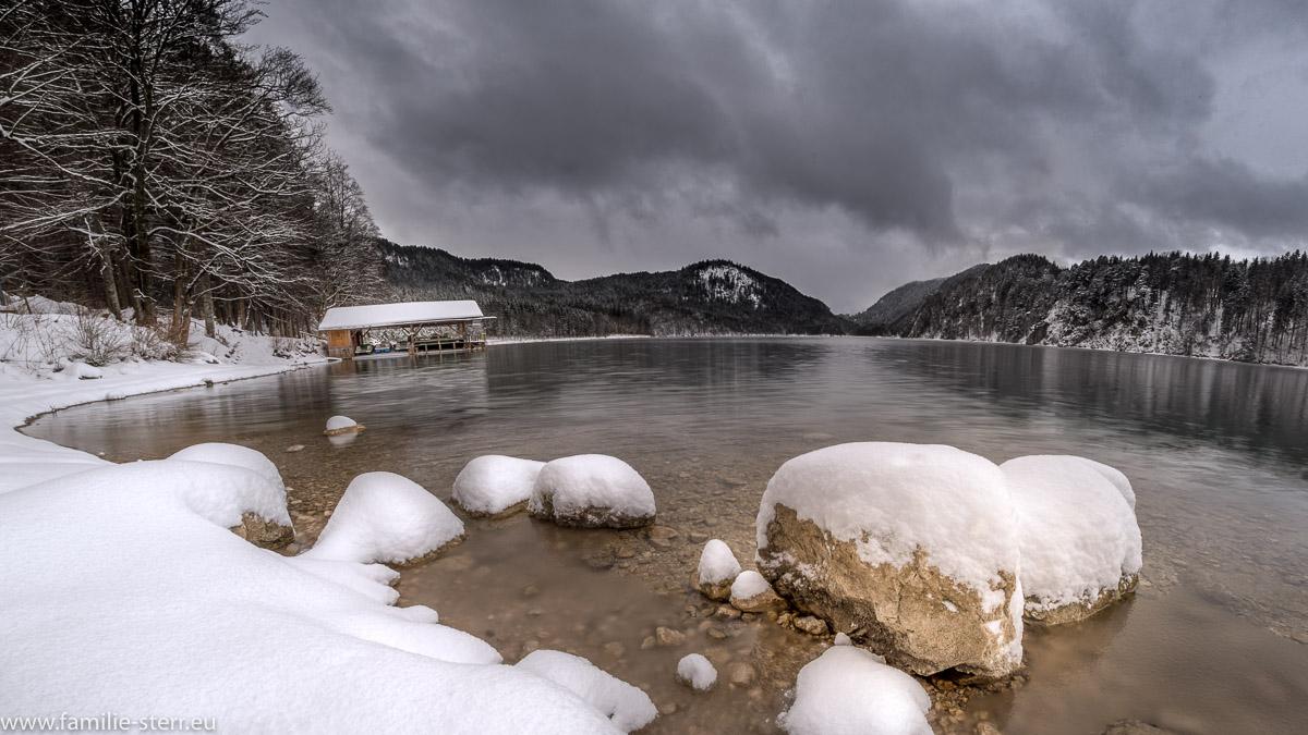 Schneebedeckte Steine im winterlichen Alpsee bei Hohenschwangau
