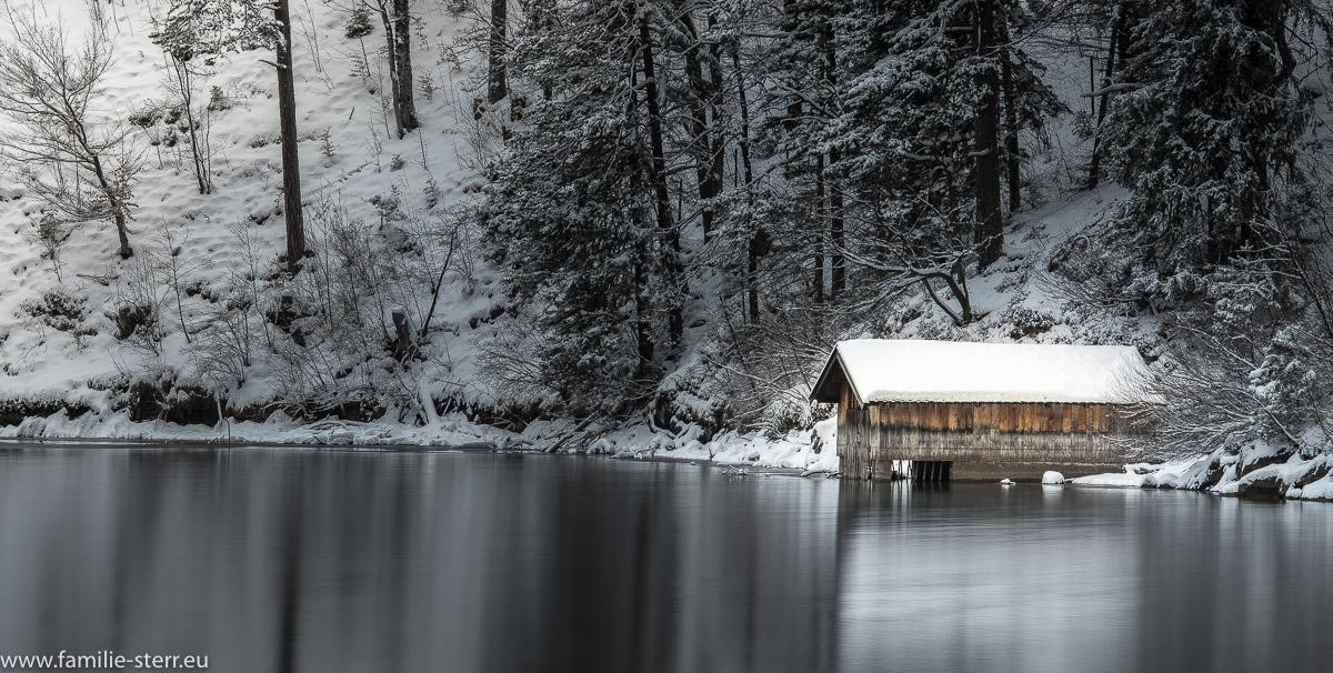 verschneites Bootshaus am winterlichen Alpsee