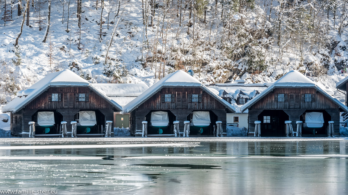 schneebedeckte Bootshäuser am vereisten Königssee