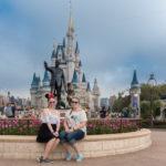 Melanie und Katharina sitzen vor der Statue von Walt Disney vor Cinderella's Castle im Magic Kingdom