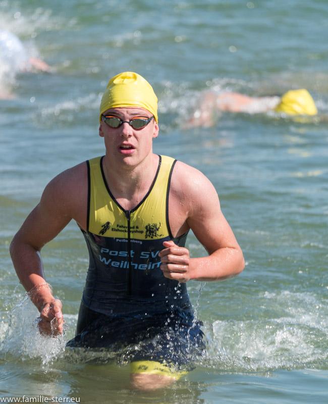 Athlet steigt am Ende des Schwimmwettbewerbs aus dem Wasser am Kronthaler Weiher