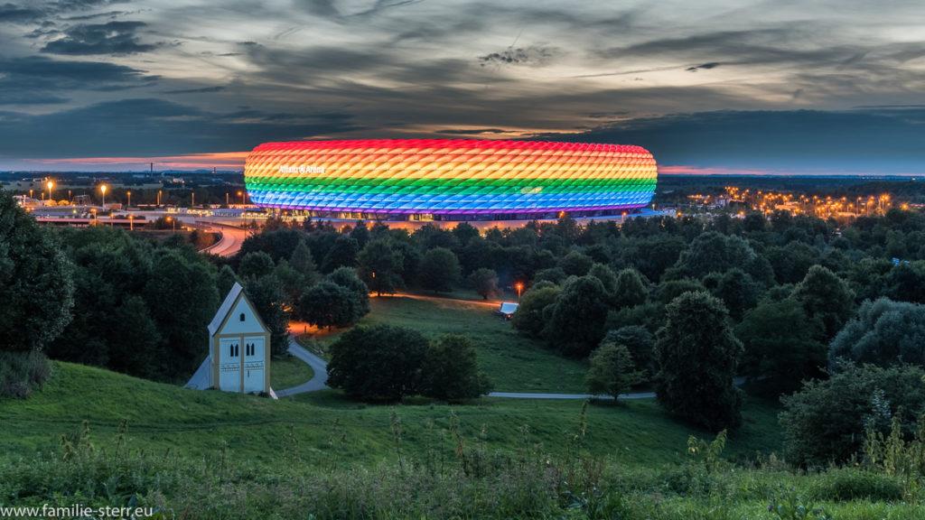 Allianz Arena und die versunkene Kirche in München in Regenbogenfarben zum Christopher Street Day 2017