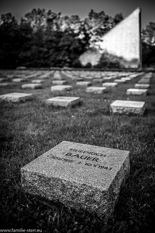 ein Name auf einem Gedenkstein in einer langen Reihe von Grabsteinen