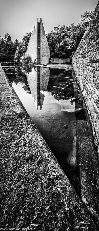 Die Gedenkhalle am Eingang der Kriegsgräberstätte spiegelt sich im Wasser