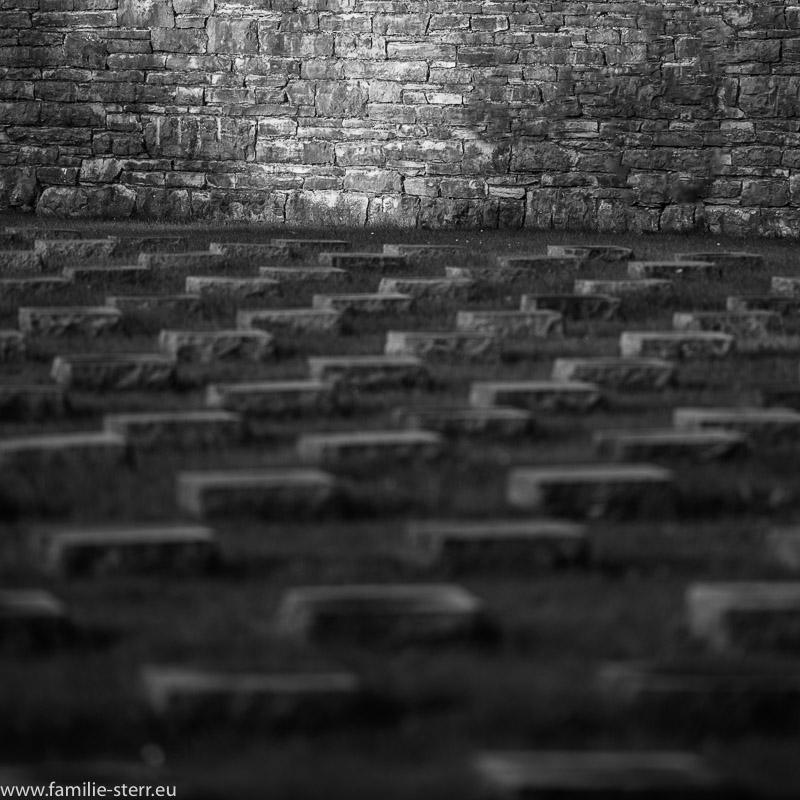 Ein Lichtstrahl erleuchtet einen Teil der Mauer an der Kriegsgräberstätte in München