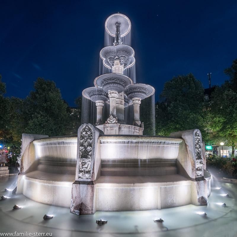 Glaspalastbrunnen am Weissenburger Platz in München Haidhausen nach Sonnenuntergang