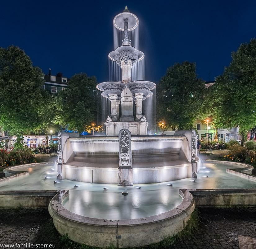 Brunnen am Weissenburger Platz in München Haidhausen nach Sonnenuntergang