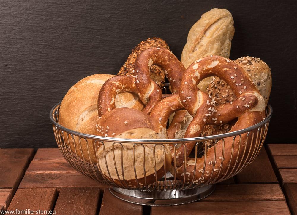 Brotkorb mit Frühstückssemmeln, Brezen und Vollkornteilen