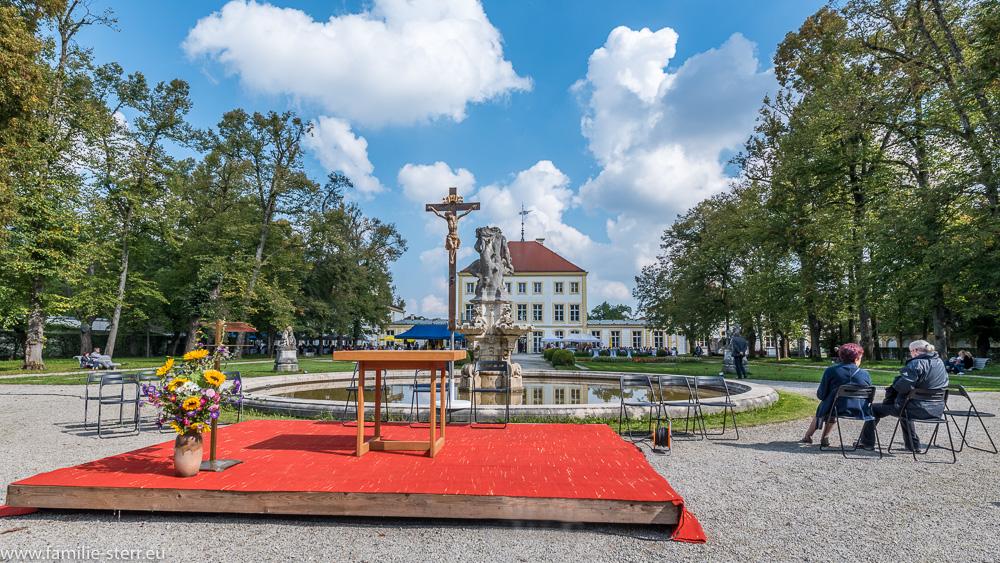 Altar und Kreuz vor dem Faunbrunnen im Barockpark am Schloss Fürstenried