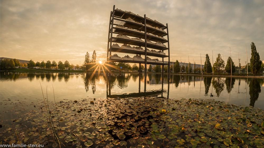"""Sonnenuntergang neben dem Kunstwerk """"Gran Paradiso"""" im Messesee an der neuen Messe München"""