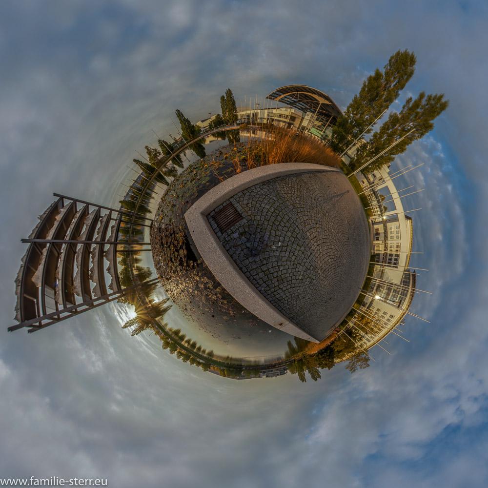 "Sonnenuntergang neben dem Kunstwerk ""Gran Paradiso"" im Messesee an der neuen Messe München als Little Planet"