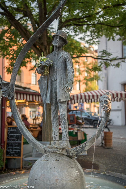 Karl Valentin Brunnen vor einen Marktstandl am Münchner Viktualienmarkt