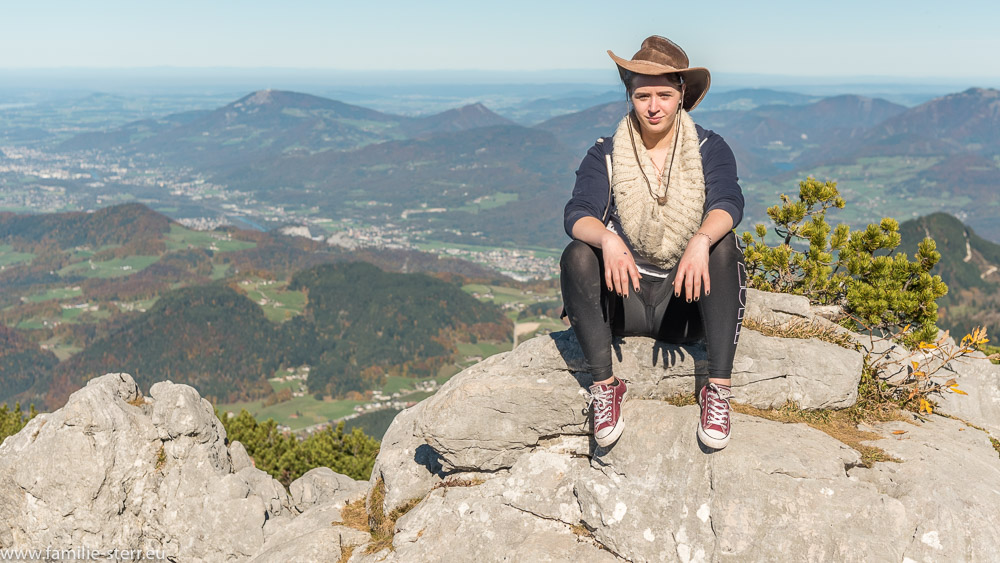 Melanie sitzt auf einem Felsen auf dem Kehlstein mit Blick über das Salzburger Land