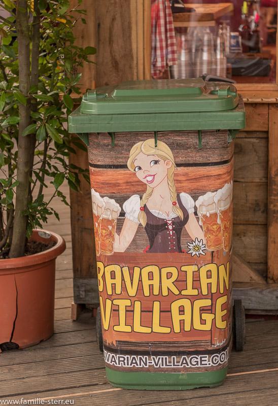 """Mülleimer mit Beschriftung """"Bavarian Village"""" und Werbefigur"""