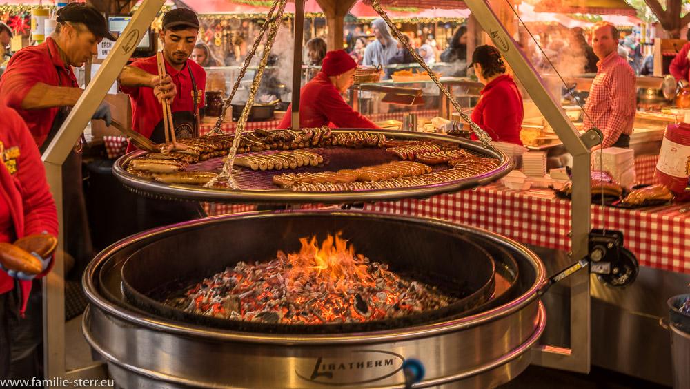 Glühende Kohle und Bratwürste auf einem Schwenkgrill im Bavarian Village