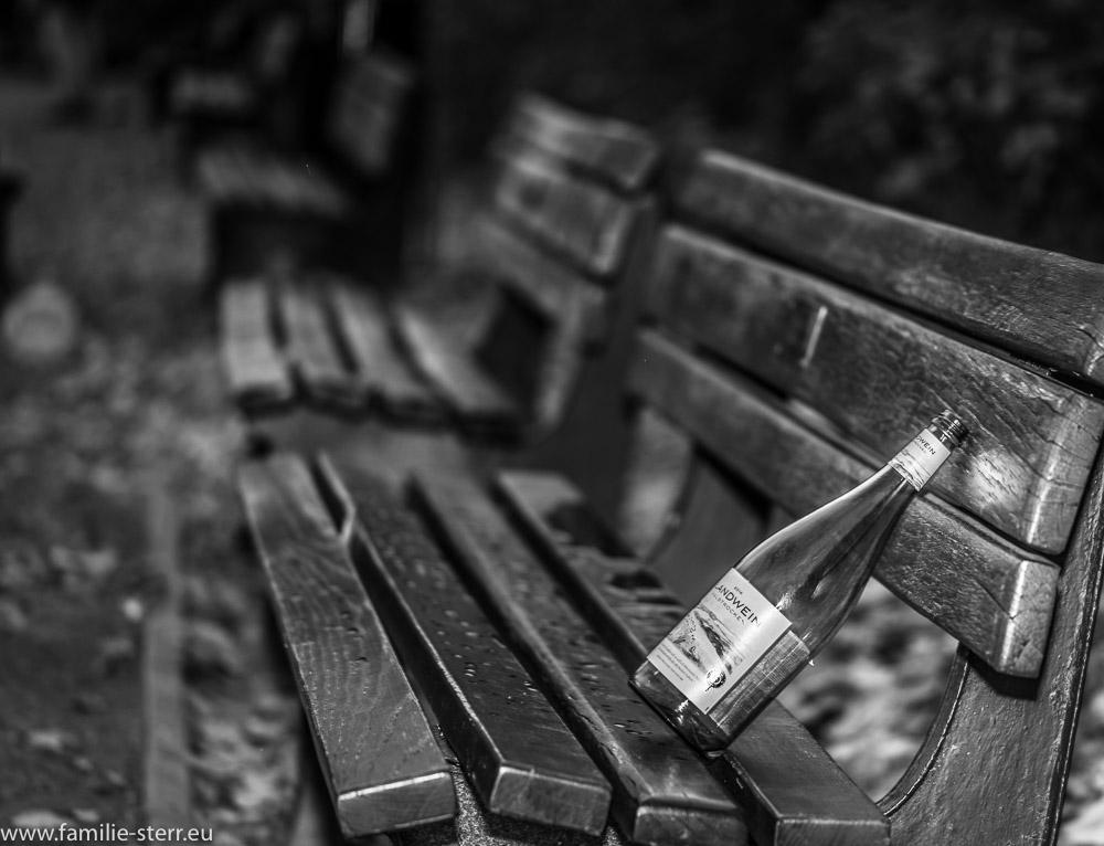 Eine einsame Weinflasche auf einer Reihe von Bänken im Hofgarten München