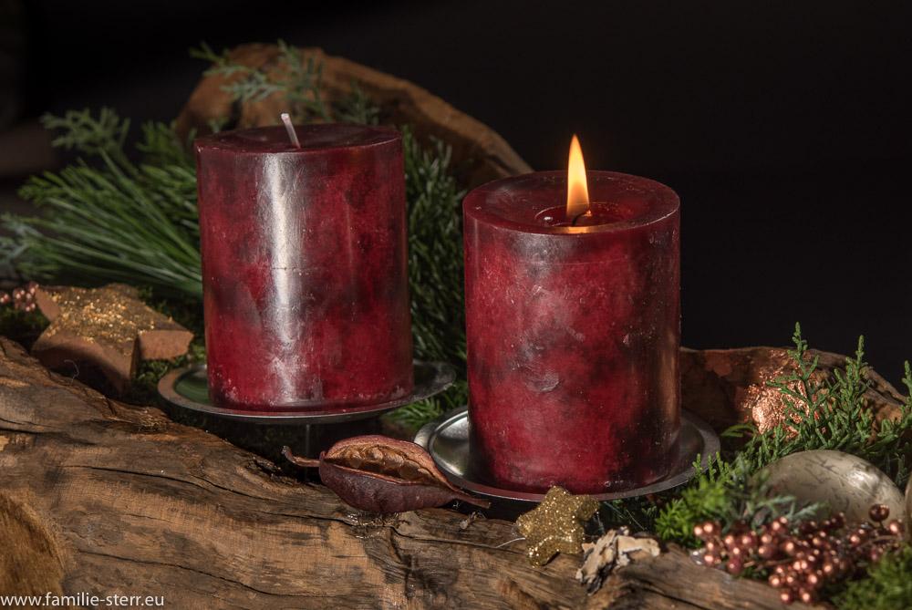 brennender Kerze auf dem Adventsgesteck in einer alten Wurzel