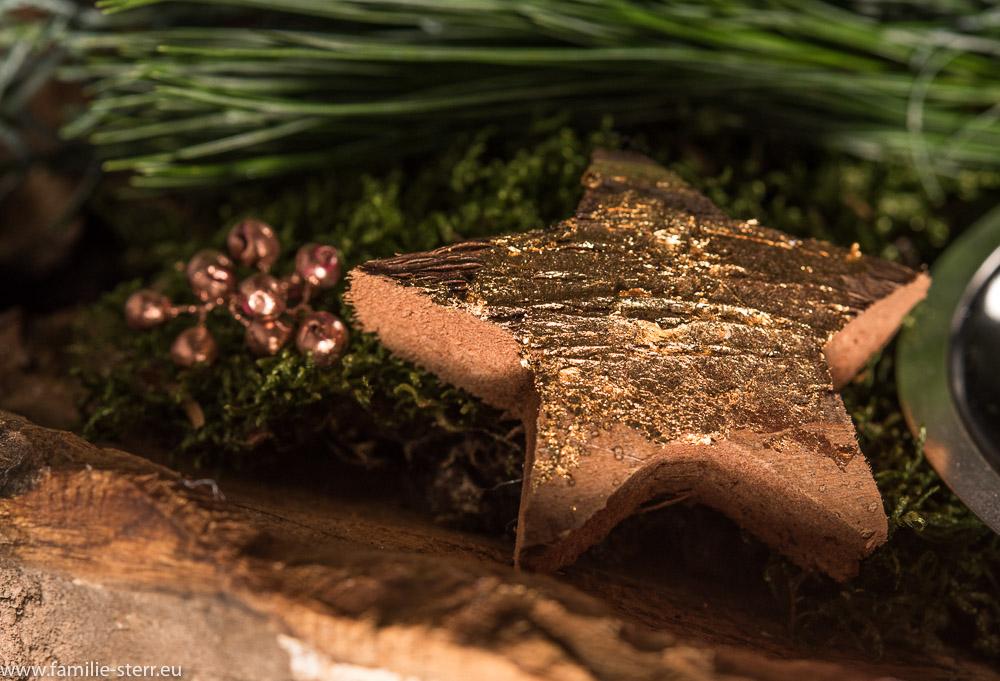 ein vergoldeter Holzstern auf unserem Adventskranz