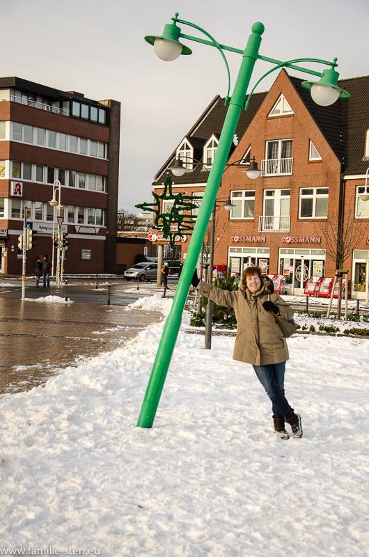 Astrid vor einer schiefen Straßenlaterne vor dem Bahnhof in Westerland