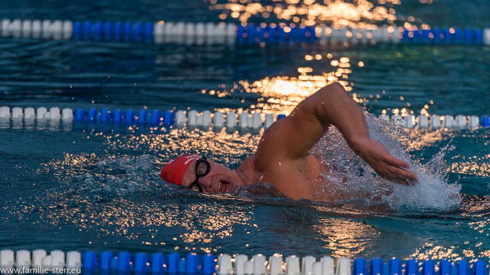 Schwimmer mit besonderem Gesichtsausdruck im Veitsbad beim Eisschwimmen im Lichtschein der nächtlichen Beleuchtung