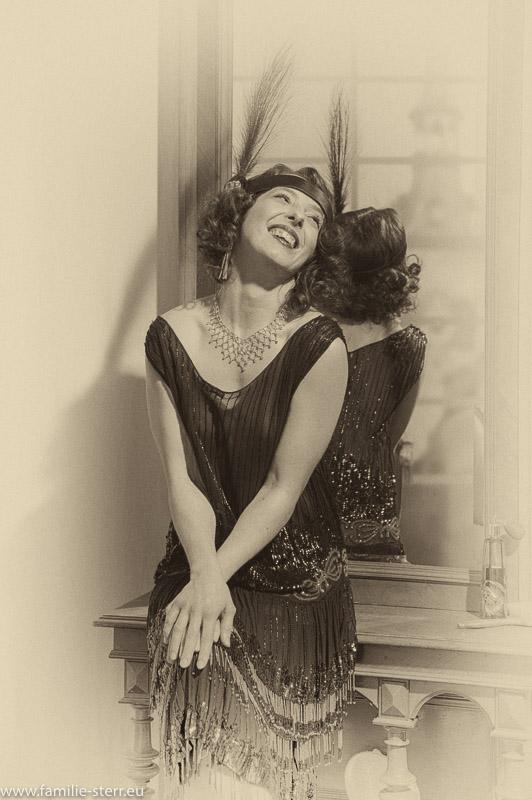Porträt im Stil der 20er Jahre von Anna vor einem alten Spiegel mit 20er Jahre Kleidchen und Feder