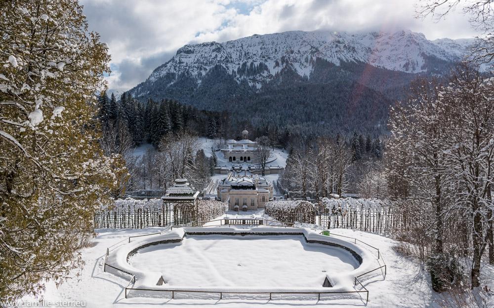 das Schloss und der Schlosspark Linderhof im tiefen Winter von einem Gartenpavillon ausgesehen