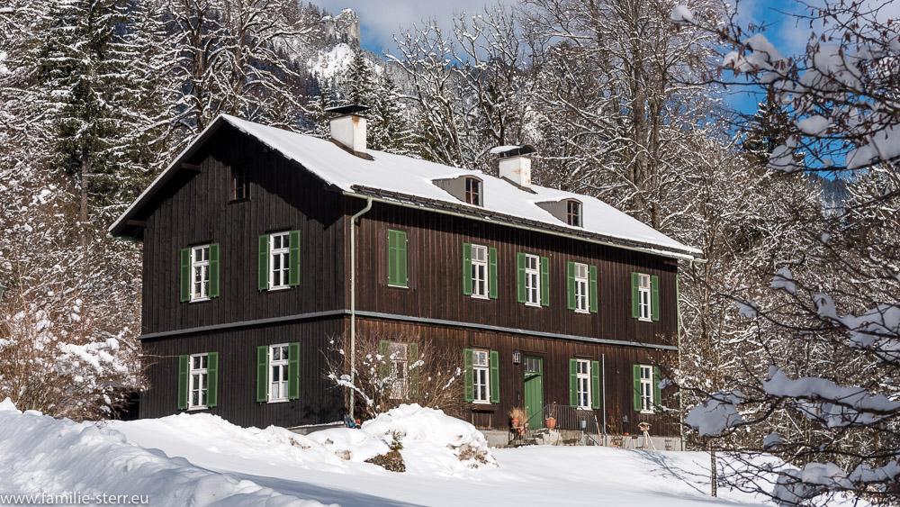 ein verschneites, holzgetäfeltes Wohngebäude im Park von Schloss Linderhof
