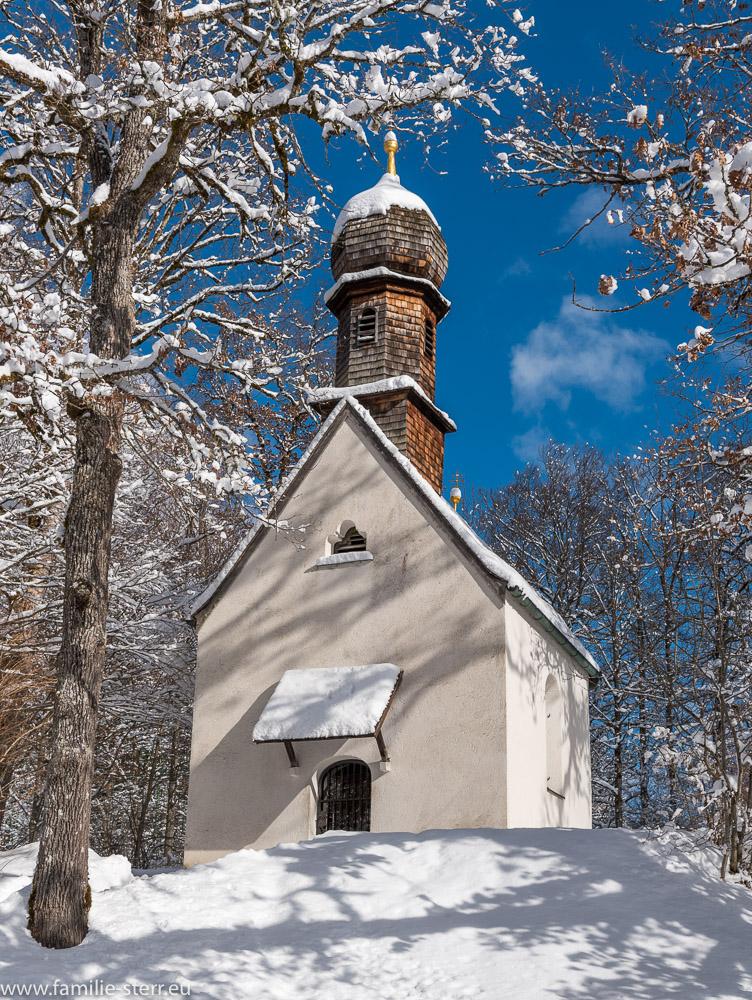 die verschneite Schlosskapelle im Schlosspark von Linderhof
