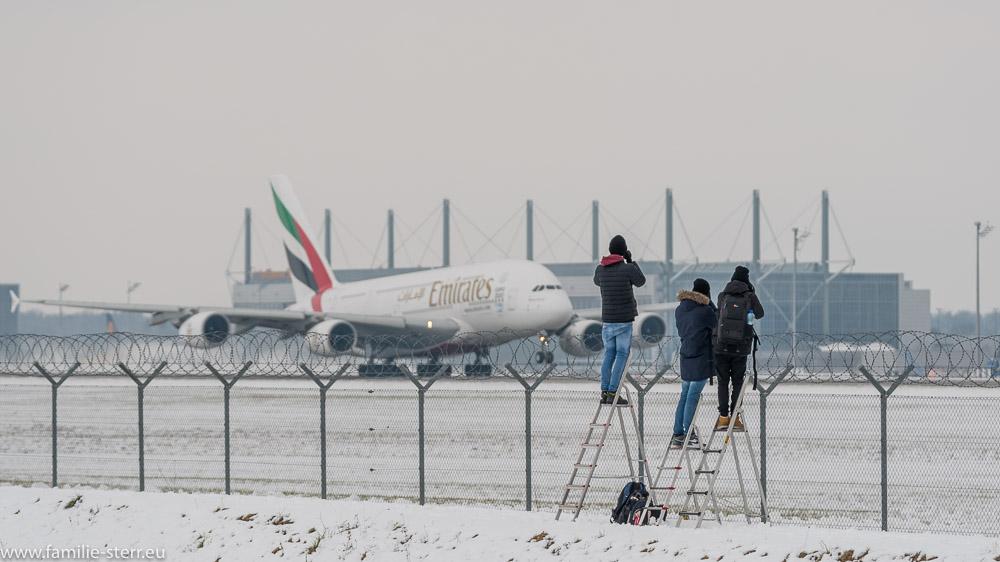 Spotter warten auf den Emirates Airbus A380 am Zaun der Startbahn am Flughafen München