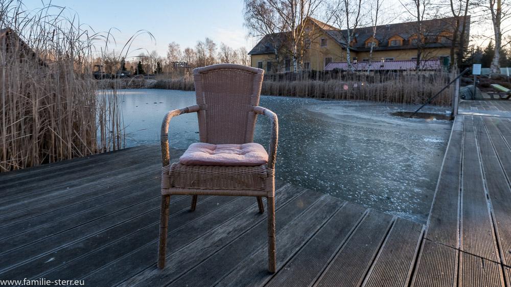 Stuhl mit Eiskristallen vor dem gefrorenen Bio - Badeteich des Seehotel Burg im Spreewald