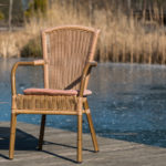 Stuhl im Sonnenschein am Rande des vereisten Bio - Badeteichs im Garten des Seehotel Burg im Spreewald