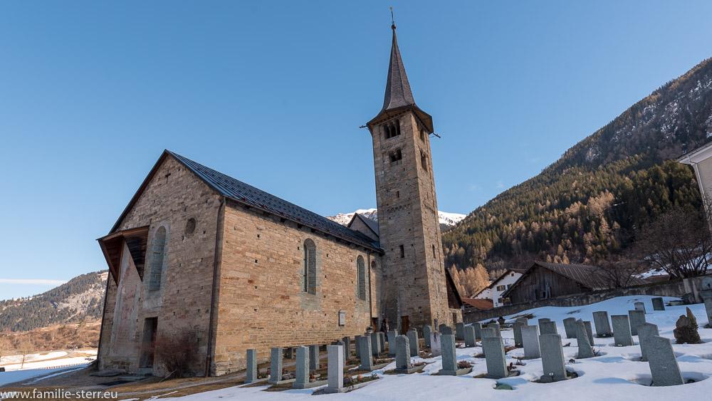 Blick über die schneebedeckten Gräber auf den romanischen Bau der St. Martin Kirche in Zillis in Graubünden