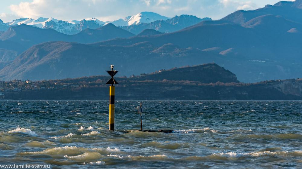 """Gefahrenzeichen """"West"""" am Gardasee vor dem schneebedeckten Monte Baldo"""