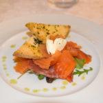 Teller mit der Vorspeise: Lachs-Carpaccio mit Toast und Creme Fraiche