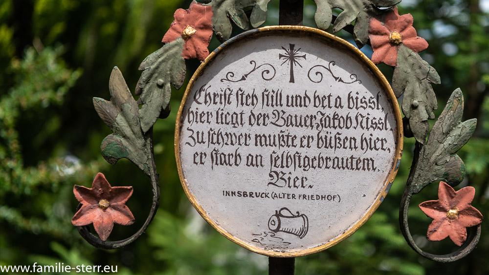 """Grabkreuz mit der Inschrift """"Christ steh still und bet a bissl, hier liegt der Bauer Jakob Nisse. Zu schwer mußte er büßen hier, er starb an selbstgebrautem Bier"""""""