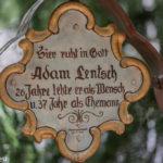 """Grabkreuz mit der Inschrift """"hier ruht in Gott Adam Lentsch, 26 Jahre lebte er als Mensch und 37 Jahr als Ehemann"""""""