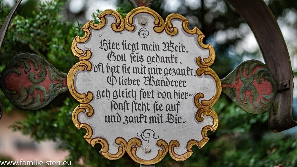 """Grabkreuz mit der Inschrift """"hier liegt mein Weib, Gott seis gedankt, oft hat sie mit mir gezankt. O lieberer Wanderer geh gleicht fort von hier, sonst steht sie auf und zankt mit Dir"""""""